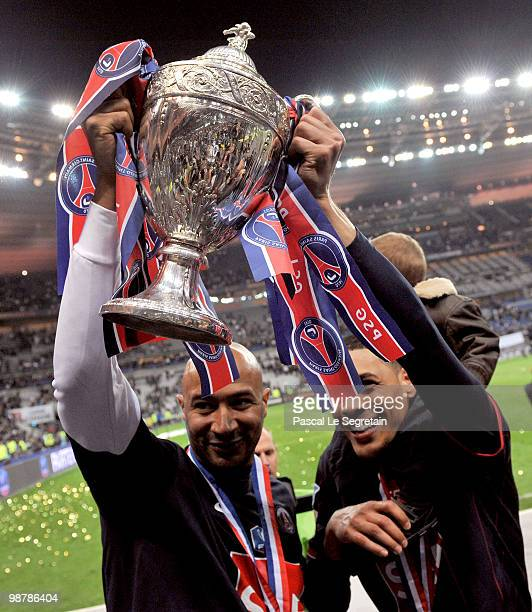 Paris SaintGermain's French defender Sammy Traore and Paris SaintGermain's French striker Guillaume Hoarau hold the trophy to celebrate the winning...