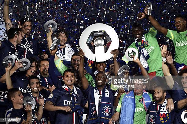 Paris Saint-Germain's French defender Zoumana Camara holds is trophy on the podium after winning the French L1 title at the end of the French L1...