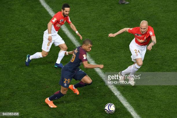 Paris SaintGermain's French forward Kylian Mbappé fights for the ball with Monaco's Portuguese midfielder Joao Moutinho and Monaco's Italian defender...