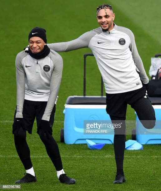 Paris SaintGermain's French forward Kylian Mbappe and French defender Layvin Kurzawa take part in a training session in SaintGermainenLaye western...