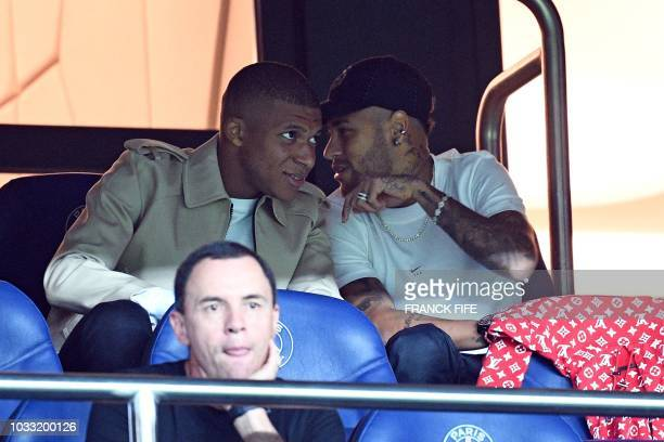 Paris Saint-Germain's French forward Kylian Mbappe and Paris Saint-Germain's Brazilian forward Neymar sit in the tribunes during the French L1...