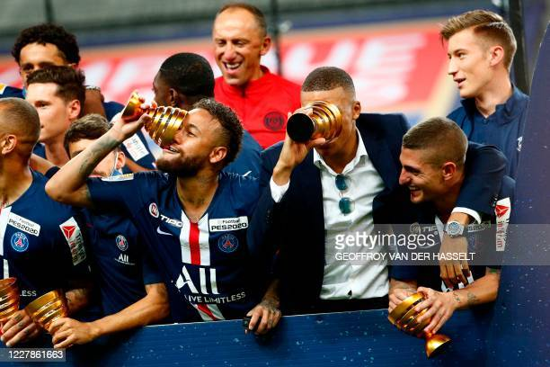 Paris Saint-Germain's French forward Kylian Mbappe and Paris Saint-Germain's Brazilian forward Neymar jokes with their trophies past teammates as...