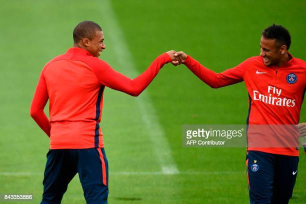 Paris SaintGermain's French forward Kylian Mbappe and Paris SaintGermain's Brazilian forward Neymar shake hands as they take part in a training...