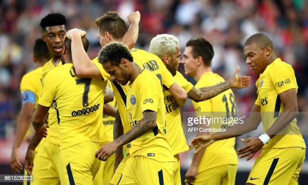 Paris SaintGermain's French forward Kylian Mbappe and Paris SaintGermain's Brazilian forward Neymar celebrate a goal with teammates during the French...