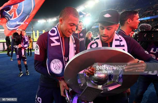 Paris Saint-Germain's French forward Kylian Mbappe and teammate Brazilian forward Neymar look at a trophy as they celebrate with teammates after...