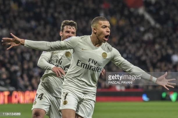 Paris SaintGermain's French forward Kylian Mbappe celebrates after scoring a goal next to Paris SaintGermain's Spanish defender Juan Bernat during...