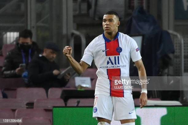 Paris Saint-Germain's French forward Kylian Mbappe celebrates after scoring a goal during the UEFA Champions League round of 16 first leg football...