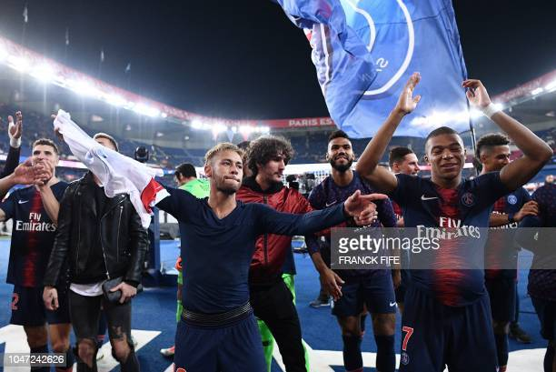 Paris Saint-Germain's French forward Kylian Mbappe celebrates with Paris Saint-Germain's Brazilian forward Neymar team mates and supporters after...