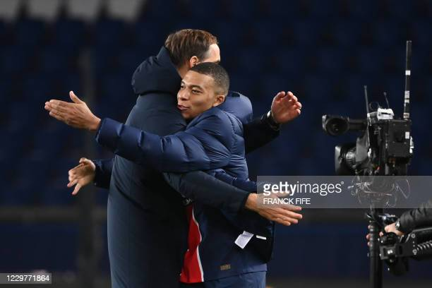 Paris Saint-Germain's French forward Kylian Mbappe celebrates with Paris Saint-Germain's German coach Thomas Tuchel after winning the UEFA Champions...