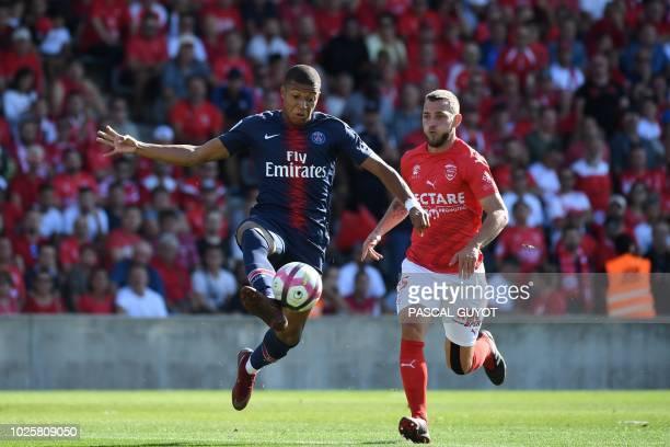 TOPSHOT Paris SaintGermain's French forward Kylian Mbappe controls the ball past Nîmes' French defender Gaetan Paquiez during the French L1 football...