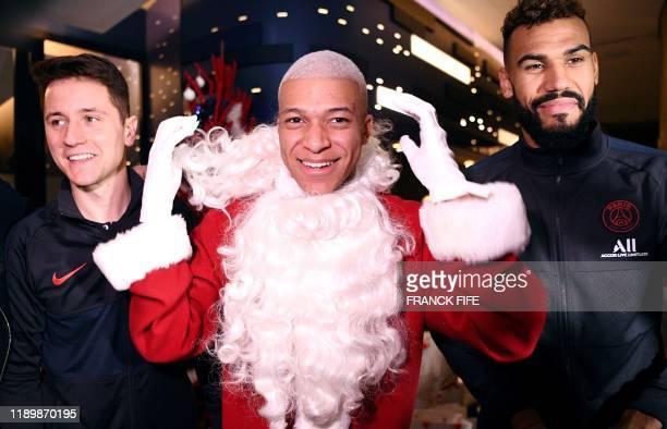 Paris Saint-Germain's French forward Kylian MBappe dressed as Santa Claus Paris Saint-Germain's Spanish midfielder Ander Herrera and Paris...