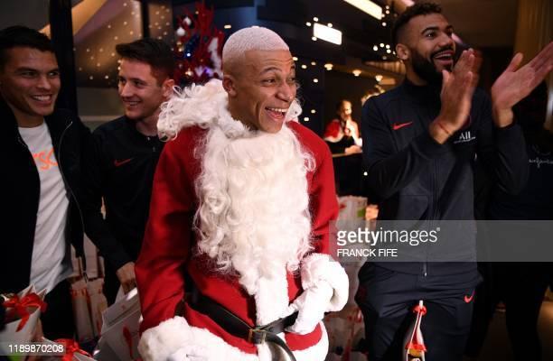 Paris Saint-Germain's French forward Kylian MBappe dressed as Santa Claus, Paris Saint-Germain's Brazilian defender Thiago Silva , Paris...