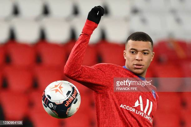 Paris Saint-Germain's French forward Kylian Mbappe eyes the ball as he warms up prior to the French L1 football match between Paris Saint-Germain and...