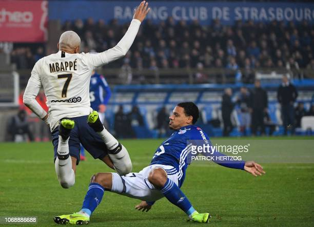 Paris SaintGermain's French forward Kylian Mbappe falls on the football as he vies for the ball with Strasbourg's French defender Kenny Lala during...