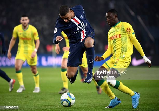 TOPSHOT Paris SaintGermain's French forward Kylian Mbappe fights for the ball with Nantes' French defender Dennis Appiah during the French L1...