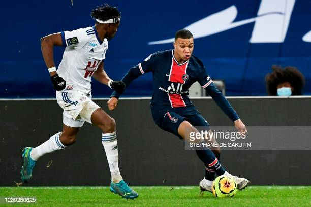 Paris Saint-Germain's French forward Kylian Mbappe fights for the ball with Strasbourg's French defender Mohamed Simakan during the French L1...