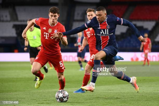 Paris Saint-Germain's French forward Kylian Mbappe fights for the ball with Bayern Munich's French defender Benjamin Pavard during the UEFA Champions...