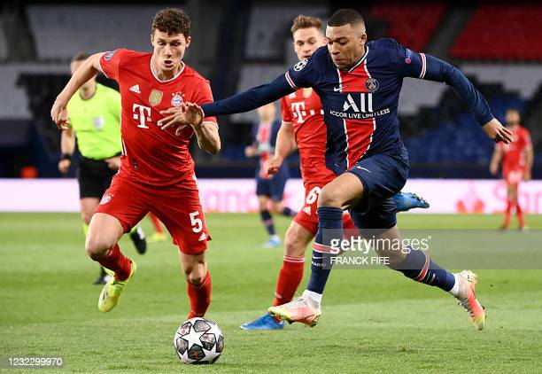 Paris Saint-Germain's French forward Kylian Mbappe fights for the ball with Bayern Munich's defender Benjamin Pavard during the UEFA Champions League...