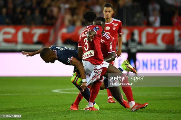 Paris Saint-Germain's French forward Kylian Mbappe fights for the ball with Brest's French defender Lilian Brassier during the French L1 football...