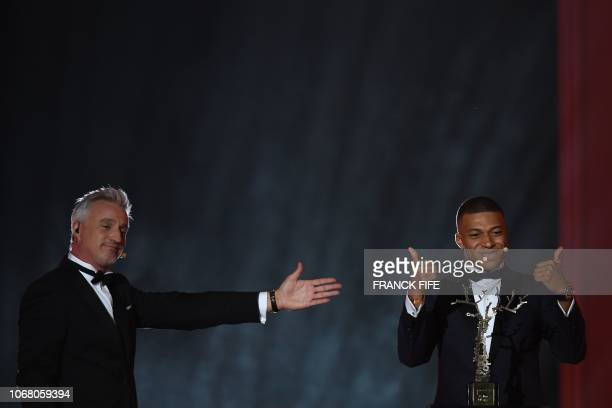 TOPSHOT Paris SaintGermain's French forward Kylian Mbappe gestures after receiving the Kopa Trophy past former French footballer and host David...