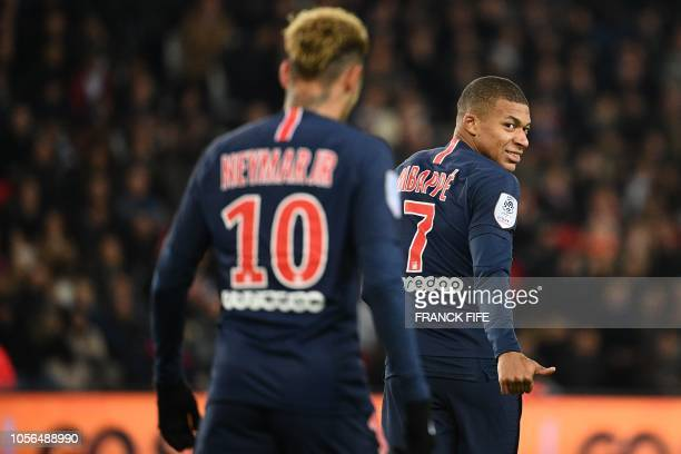 Paris SaintGermain's French forward Kylian Mbappe gestures and smiles towards Paris SaintGermain's Brazilian forward Neymar during the French L1...