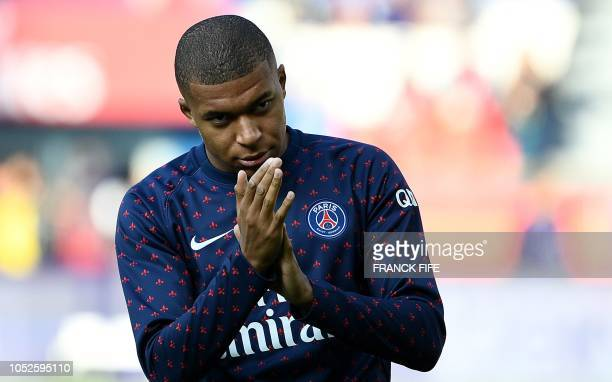 TOPSHOT Paris SaintGermain's French forward Kylian Mbappe gestures as he warms up with teammates ahead of the the French L1 football match between...