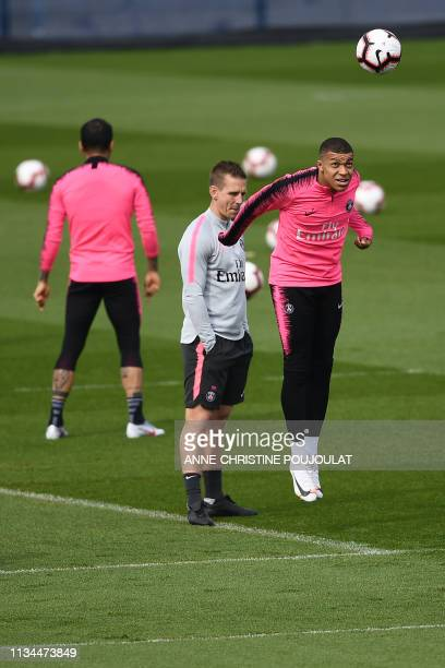 Paris SaintGermain's French forward Kylian Mbappe heads the ball during a training session at the club's Camp des Loges training grounds in...