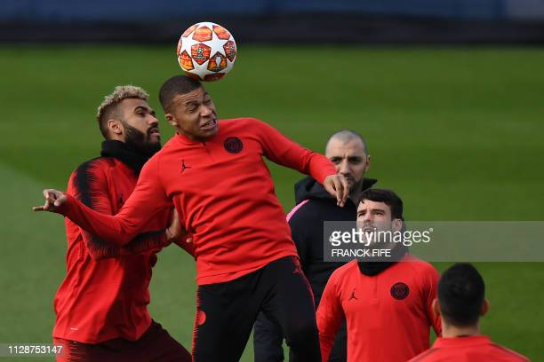 Paris SaintGermain's French forward Kylian Mbappe heads the ball with Paris SaintGermain's Cameroonian forward Eric ChoupoMoting during a training...