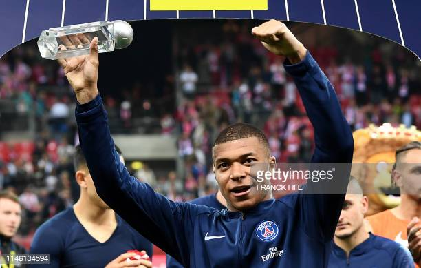 TOPSHOT Paris SaintGermain's French forward Kylian Mbappe holds a trophy for 'best stricker' at the end of the French L1 football match between Reims...