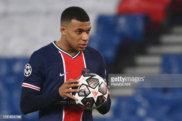 Paris Saint-Germain's French forward Kylian Mbappe holds the ball before kicking a penalty kick during the UEFA Champions League round of 16 second...