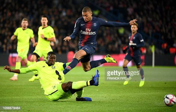 TOPSHOT Paris SaintGermain's French forward Kylian Mbappe is tackled by Lille's French defender Adama Soumaoro during the French L1 football match...