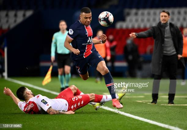 Paris Saint-Germain's French forward Kylian Mbappe is tackled by Monaco's Chilean defender Guillermo Maripan during the French L1 football match...