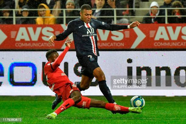 Paris Saint-Germain's French forward Kylian Mbappe is tackled during the French L1 football match between Dijon Football Cote-d'Or and Paris...