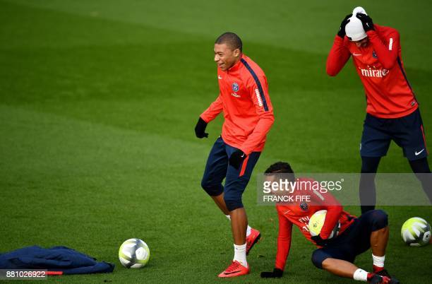 Paris SaintGermain's French forward Kylian MBappe jokes with Paris SaintGermain's Brazilian defender Marquinhos during a training session in...