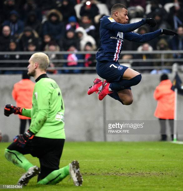 Paris SaintGermain's French forward Kylian Mbappe jumps as he vies for the ball with Reims' Serbian goalkeeper Predrag Rajkovic during the French...