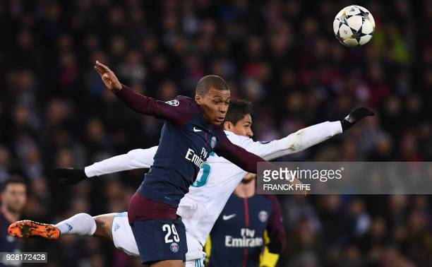 TOPSHOT Paris SaintGermain's French forward Kylian Mbappe jumps for the ball with Real Madrid's French defender Raphael Varane during the UEFA...