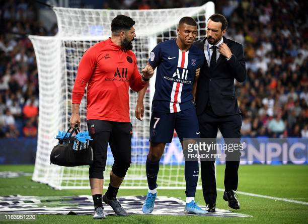 TOPSHOT Paris SaintGermain's French forward Kylian Mbappe leaves the pitch following an injury during the French L1 football match between Paris...
