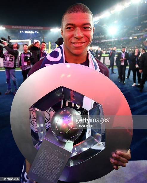 Paris Saint-Germain's French forward Kylian Mbappe poses with a trophy as he celebrates with teammates after winning the French L1 title at the end...