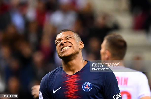 TOPSHOT Paris SaintGermain's French forward Kylian Mbappe reacts after missing a shot on goal during the French L1 football match between Reims and...