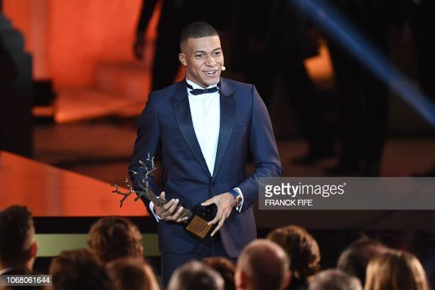 TOPSHOT Paris SaintGermain's French forward Kylian Mbappe reacts after receiving the Kopa Trophy during the 2018 Ballon d'Or award ceremony at the...