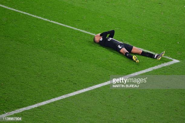 TOPSHOT Paris SaintGermain's French forward Kylian Mbappe reacts as he lies on the pitch at the end of the UEFA Champions League round of 16...