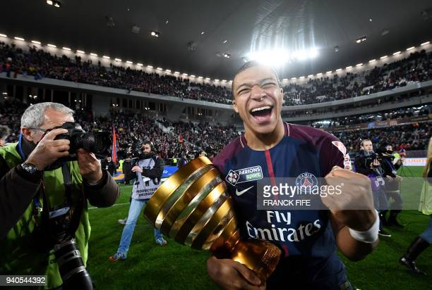 Paris SaintGermain's French forward Kylian Mbappe reacts with the trophy after winning the French League Cup final football match between Monaco and...