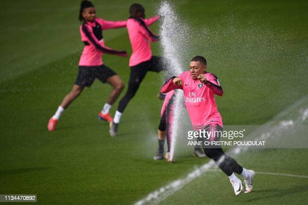 TOPSHOT Paris SaintGermain's French forward Kylian Mbappe runs past sprinklers as he attends a training session at the club's Camp des Loges training...