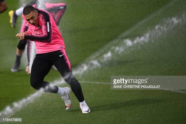 Paris SaintGermain's French forward Kylian Mbappe runs past sprinklers as he attends a training session at the club's Camp des Loges training grounds...