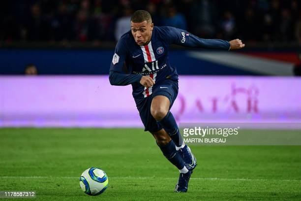 Paris Saint-Germain's French forward Kylian Mbappe runs with the ball during the French L1 football match between Paris Saint-Germain and Olympique...