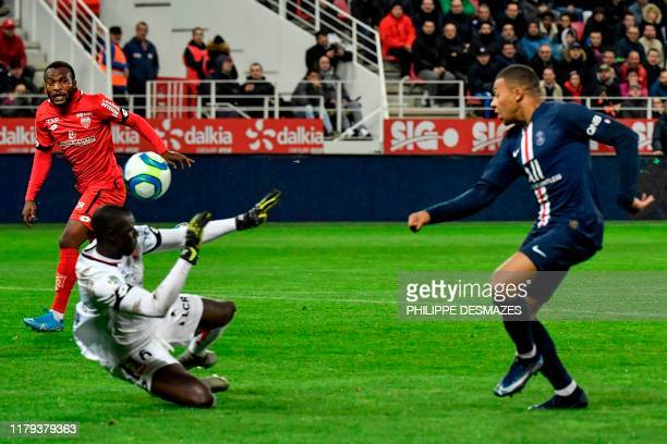 Paris Saint-Germain's French forward Kylian Mbappe scores a goal against Dijon's Senegalese goalkeeper Alfred Gomis during the French L1 football...