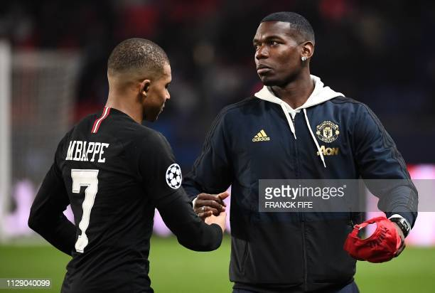 Paris SaintGermain's French forward Kylian Mbappe shakes hands with Manchester United's French midfielder Paul Pogba at the end of the UEFA Champions...