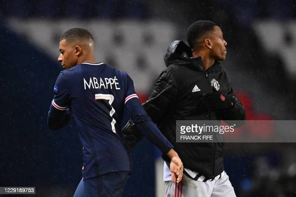Paris SaintGermain's French forward Kylian Mbappe shakes hands with Manchester United's French forward Anthony Martial after the during the UEFA...