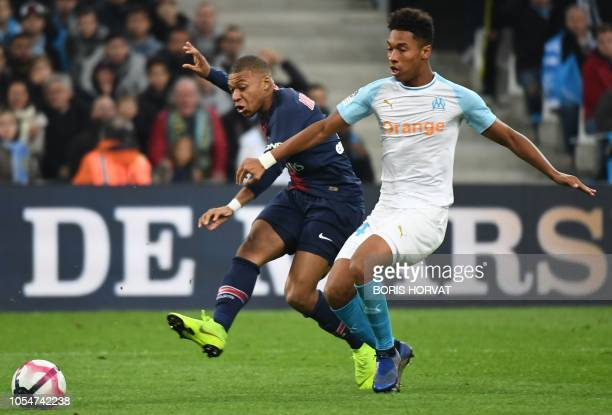 Paris Saint-Germain's French forward Kylian Mbappe shoots and scores a goal as he vies with Marseille's French defender Boubacar Kamara during the...