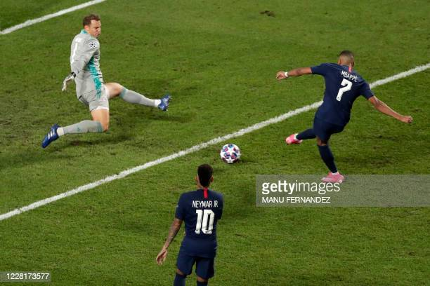 TOPSHOT Paris SaintGermain's French forward Kylian Mbappe shoots on goal against Bayern Munich's German goalkeeper Manuel Neuer despite the referee...